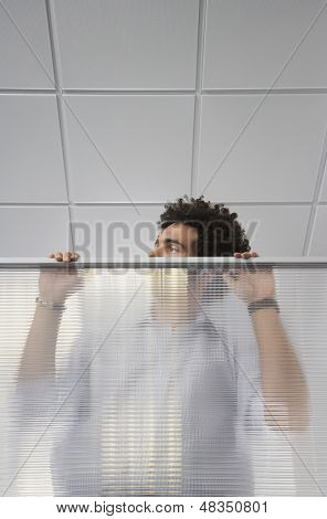 Young male office worker peering over cubicle wall in the office