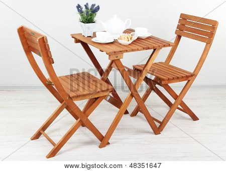 Wooden table with tea table setting in room