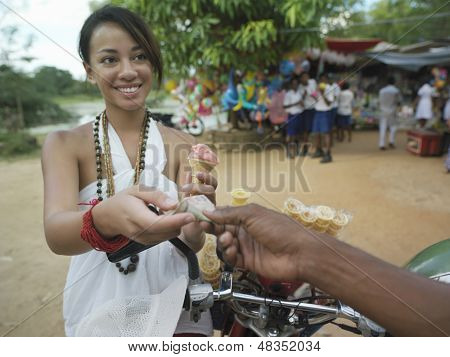 Smiling young mixed race woman paying for icecream at street market