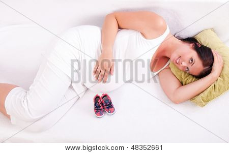 Pregnant woman lying on the sofa in front of baby boots.