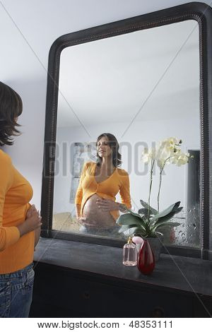 Young pregnant woman admiring stomach in bedroom mirror