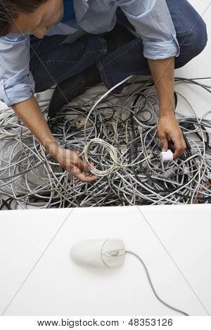 Elevated view of a cropped man working on tangled computer wires in office