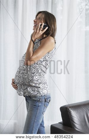Side view of a young pregnant woman using mobile phone in living room