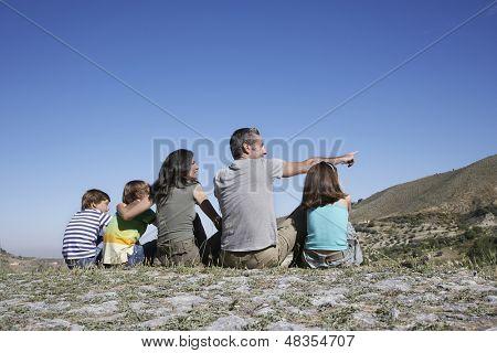 Vista trasera de una pareja con tres niños sentados en la cima de la montaña contra el cielo azul