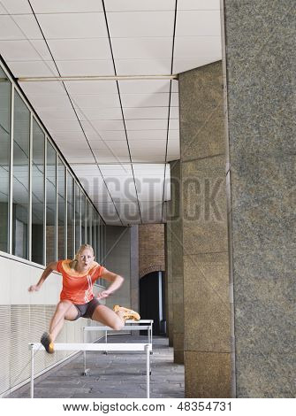 Voller Länge einer jungen Frau springen Hürden im Portikus