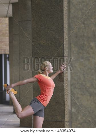 Side view of a young woman stretching against pillar in portico