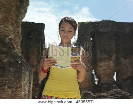 Young mixed race woman reading guidebook with ancient ruins in the background