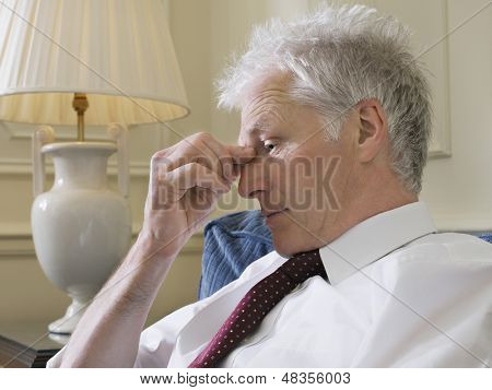 Closeup side view of a middle aged businessman pinching bridge of nose on couch