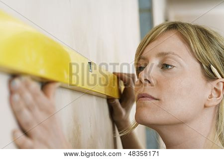 Closeup of a blond young woman using spirit level