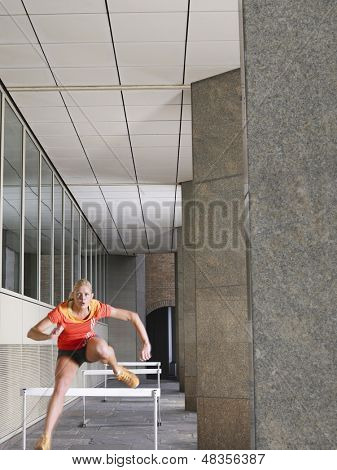 Full length of a young woman jumping hurdles in portico