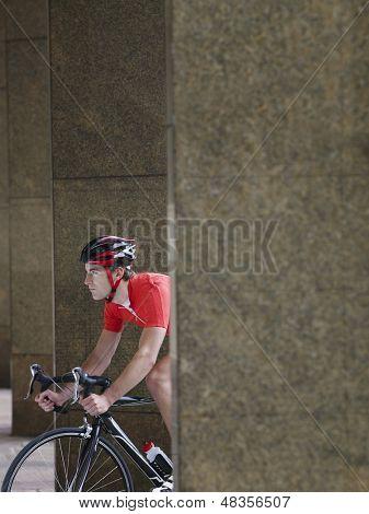 Seitenansicht eines jungen Mannes, das Radfahren zwischen den Säulen im Portikus