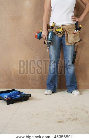 Lowsection einer jungen Frau mit Toolbelt und Bohren an die Wand gelehnt