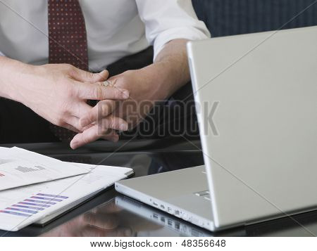 Closeup of businessman sitting on sofa by laptop with hands clasped