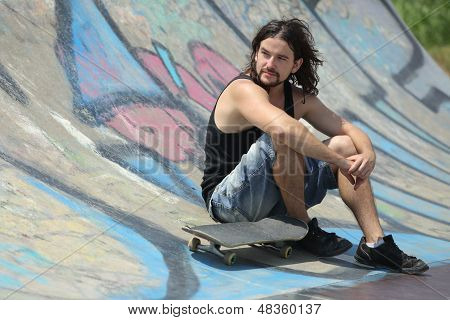 Boy Sitting With A Skateboard On A Half Pipe