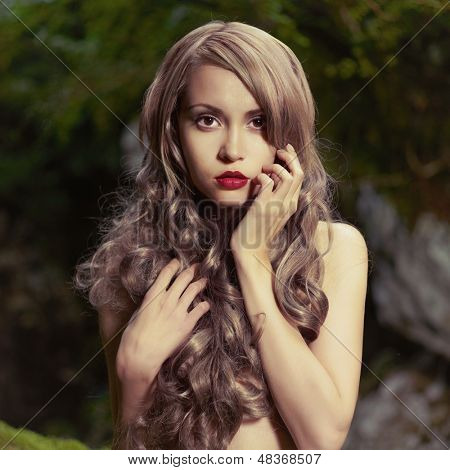 Portrait of elegant woman with luxurious hair in a coniferous forest