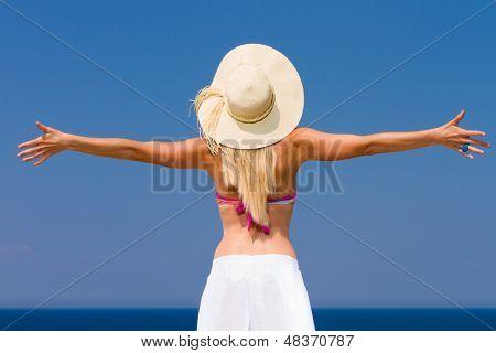 Happy woman enjoying beach relaxing joyful in summer by tropical blue water.