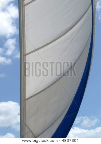 Wind In The Sail Against A Cloudy Blue Sky