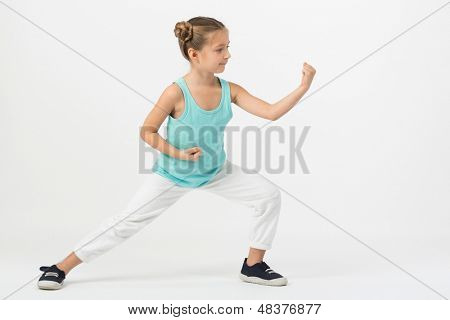 A girl with outstretched fist standing in a fighting stance