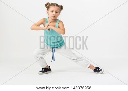 A girl is standing in a fighting stance with outstretched leg