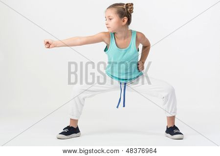 A girl is standing in a fighting stance with outstretched fist