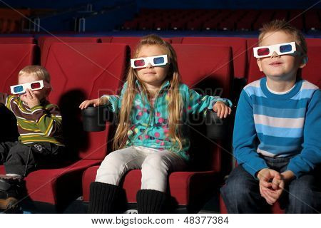 Three small children in 3D glasses watching a movie in the cinema