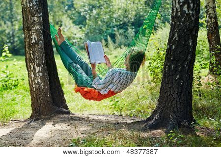 Young woman in dark sunglasses lies in hammock suspended between two thick birches and reads book