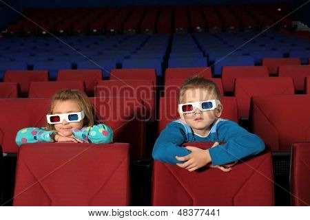 Two small children in 3D glasses watching a movie with interest in the cinema