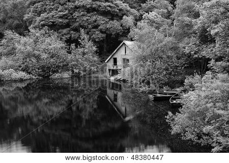 Black And White Retro Style Picture Of Derelict Boathouse And Rowing Boats Landscape Hidden In Trees