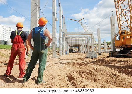 two builder workers at construction site during concrete pole and beam installation