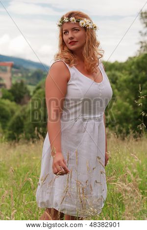 Young blond plus-size model with flower wreath in her hair and white dress standing in tall grass