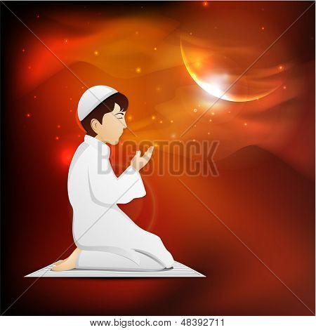 Young Muslim boy in traditional dress praying (Namaz, Islamic prayer) in shiny moon light night for Eid Mubarak festival.