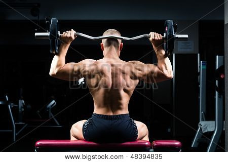Strong man - bodybuilder with dumbbells in a gym, exercising with a dumbbell