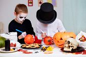 image of antichrist  - Photo of two eerie boys drawing on pumpkins at Halloween table  - JPG