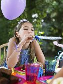 Young girl blowing party puffer at outdoor birthday party