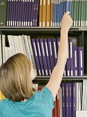 image of shelving unit  - Rear view of a young woman reaching for book from library shelf - JPG
