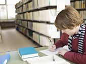foto of shelving unit  - Young male student doing homework on table in the library - JPG