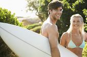 picture of watersports  - Portrait of young man carrying surfboard with girlfriend in bikini at beach - JPG