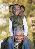 stock photo of granddaughters  - Grandfather carrying granddaughter on shoulders - JPG