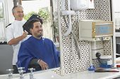 foto of barbershop  - Senior hairdresser showing finished haircut to man at barbershop - JPG
