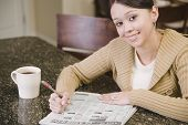 Hispanic woman searching newspaper classified ads