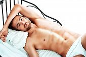 stock photo of men underwear  - Handsome nude man lying in a bed - JPG