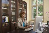 stock photo of shelving unit  - Smiling middle aged woman using computer in study room at home - JPG