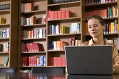 image of shelving unit  - Beautiful and serious young woman using laptop in the library - JPG