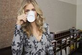 pic of shelving unit  - Portrait of a smiling young blond woman drinking coffee in office - JPG