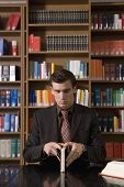 picture of shelving unit  - Young man in suit opening a book on desk in the library - JPG