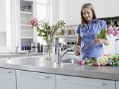 Middle aged woman preparing flowers to be put in vase at kitchen sink