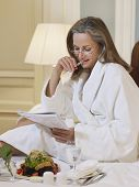 Portrait of a middle aged woman in bathrobe reading documents in bed