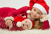 stock photo of santa baby  - Smiling little girl with cute baby boy lie in the hats of Santa Claus - JPG