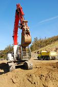 pic of track-hoe  - Large track hoe exchavator working a dirt pile at a new commercial construction site in Roseburg Oregon - JPG