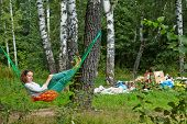 pic of birchwood  - Young barefooted woman with discontented face lies in hammock at birchwood near pile of garbage - JPG
